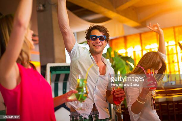 Group of friends dancing with cocktails in bar