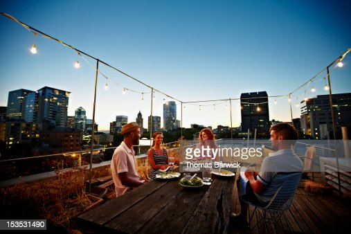 Group of friends dining at table on rooftop deck