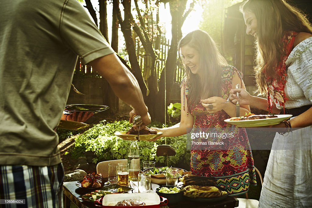 Group of friends dishing up food at table