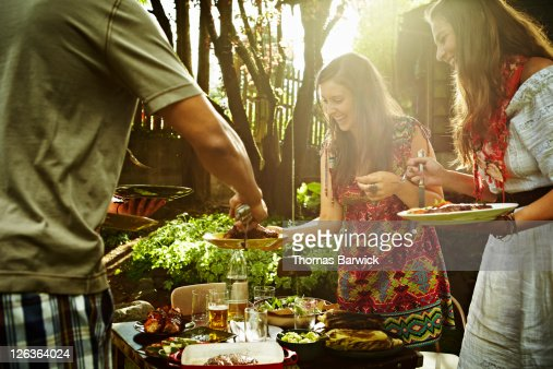 Group of friends dishing up food at table : Stock Photo