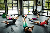 Group of friends doing abs workout on floor of gym