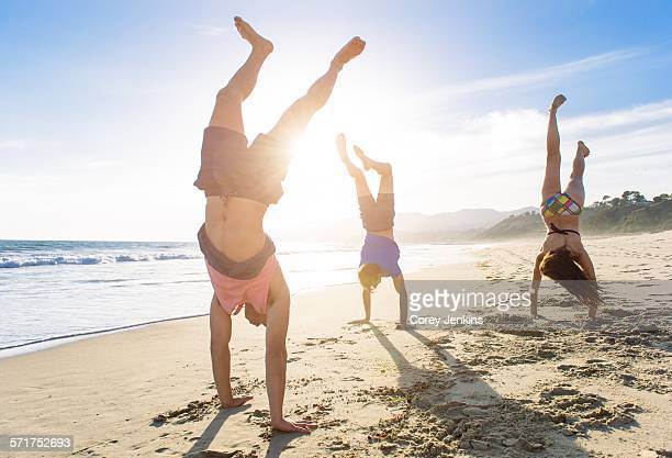 Group of friends doing handstands on beach