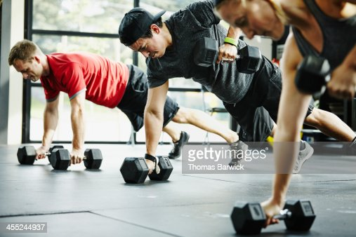 Group of friends doing pushups with dumbbells