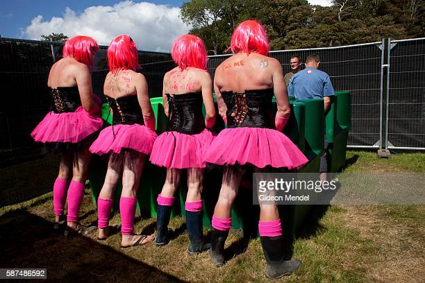A group of friends dressed up in pink tutus urinate in the men's pissoir at Camp Bestival which takes place at Lulworth Castle in Dorset They were a...