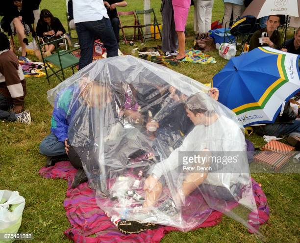 A group of friends drink alcohol and shelter from the rain under a plastic sheet on Derby Day at Epsom Downs Racecourse June 2001