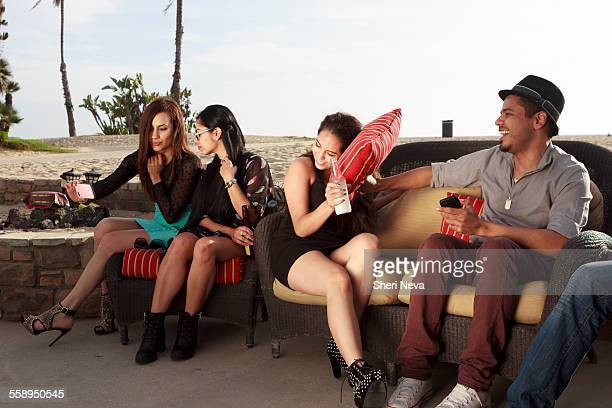 Group of friends drinking at a beach bar looking at smart phone and being playful