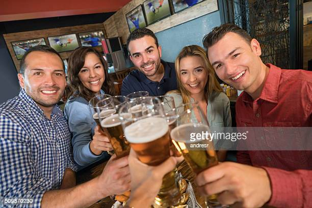 Group of friends drinking at a sports bar