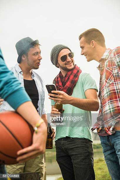 Group of friends drinking beer and looking at cell phone