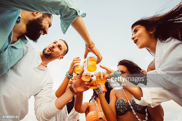 Group of friends drinking beer at beach party
