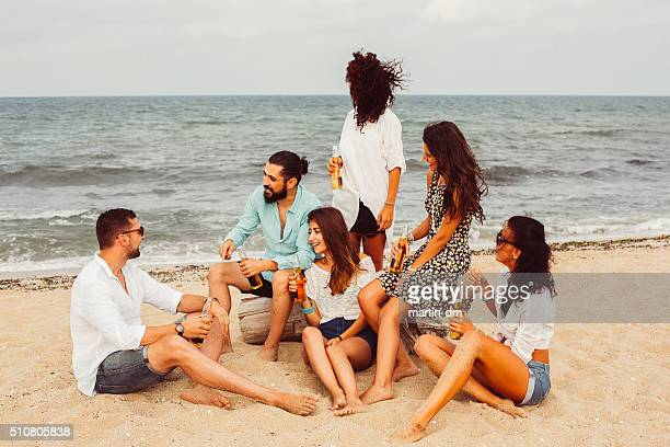 Group of friends drinking beer at the beach