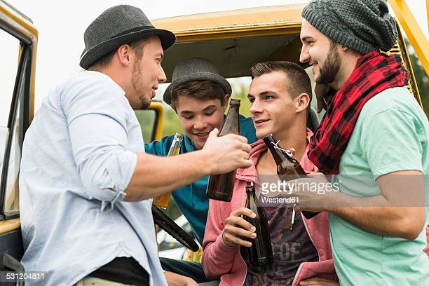 Group of friends drinking beer in car