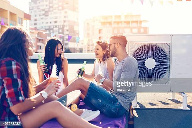 Gruppe der Freunde trinken Bier auf dem Dach