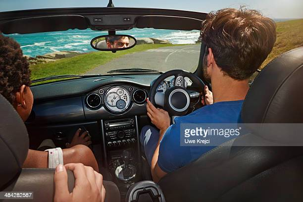 Group of friends driving convertible by the sea