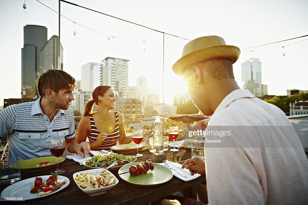 Group of friends eating at table on rooftop deck : Stock Photo