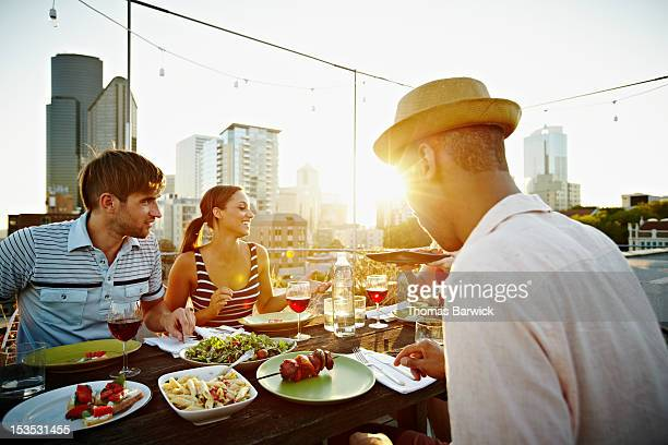 Group of friends eating at table on rooftop deck