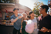 Group of friends having fun while eating cotton candy at fairground. Young man and women with candyfloss at amusement park.