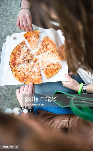 group of friends eating pizza togetherness on the park : Stock Photo