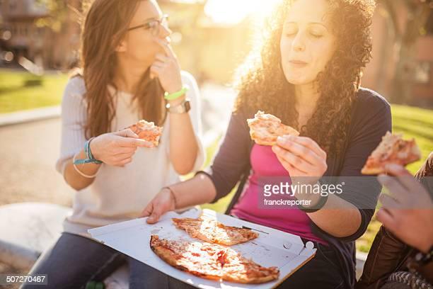 Grupo de amigos comiendo una pizza Unión
