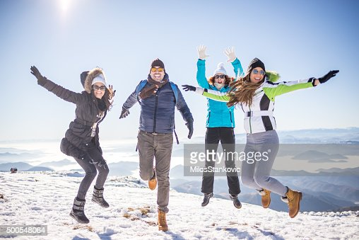 Group of friends enjoy at the top of mountain