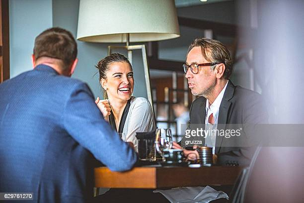 Group of friends enjoy chatting during lunch time at restaurant