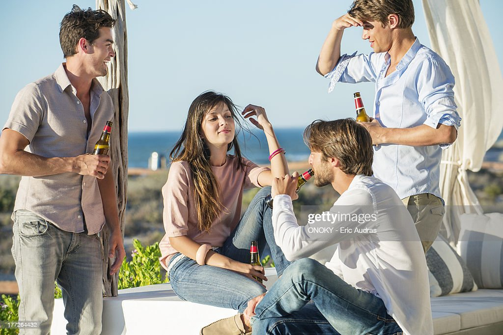 Group of friends enjoying beer outdoors on vacation : Stock Photo