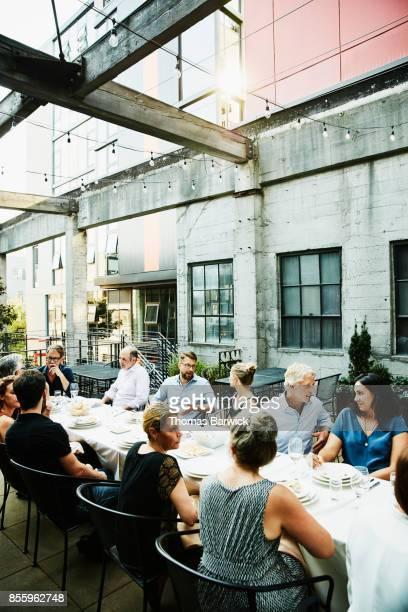 Group of friends enjoying celebration dinner on restaurant patio