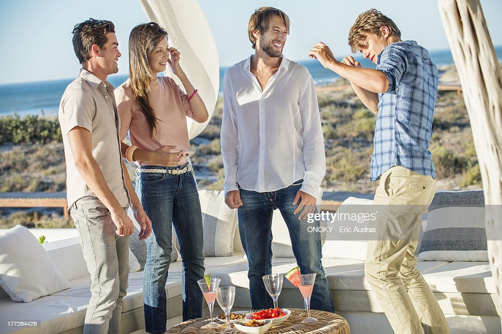 Group of friends enjoying drinks and dancing outdoors on a vacation : Stock Photo