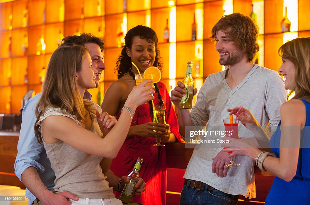 Group of friends enjoying drinks in bar : Stock Photo