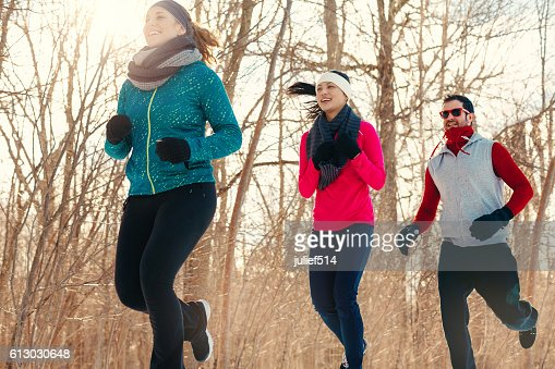 Group of friends enjoying jogging in the snow in winter : Stock Photo