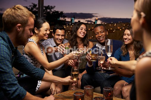 Group Of Friends Enjoying Night Out At Rooftop Bar : Stock Photo