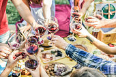 Group of friends enjoying picnic while drinking red wine and eating snack appetizer outdoor - Young people cheering and having fun together - Focus on right bottom hands glasses - Vintage filter