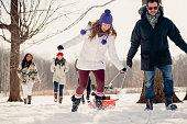 Group of millenial young adult friends enjoying wintertime and sledding in a snow filled park
