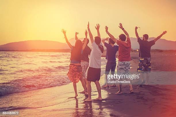 group of friends enjoying sunset on the beach