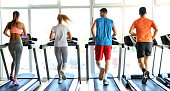 Group of friends exercising on treadmill machine in gym