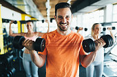 Group of friends exercising together in gym with dumbbells