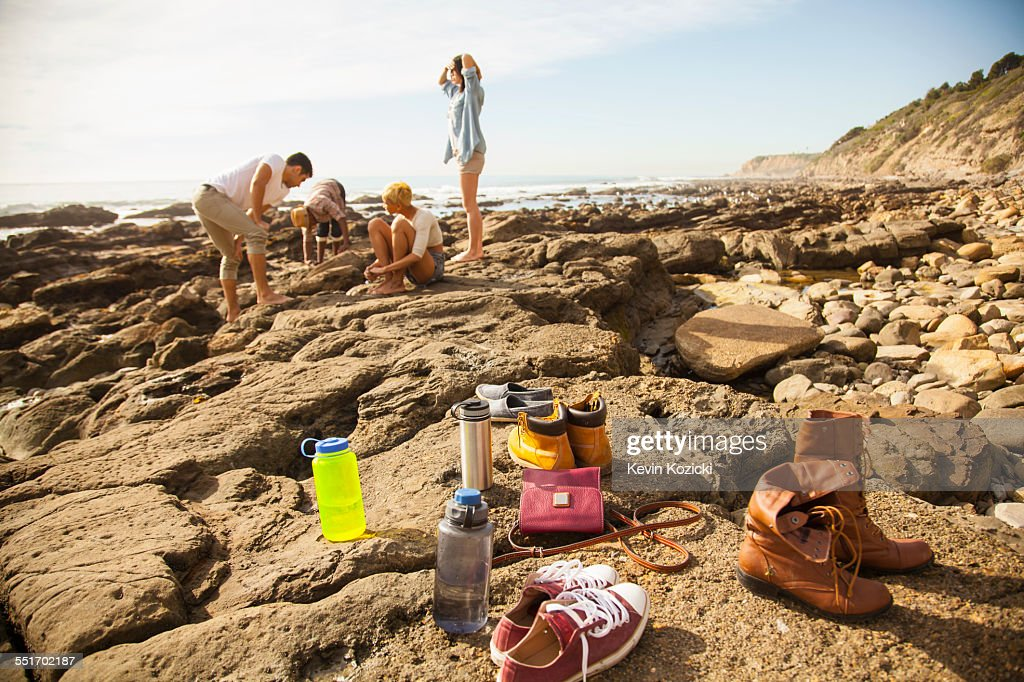 Group of friends exploring rock pools on beach, shoes and belongings in foreground