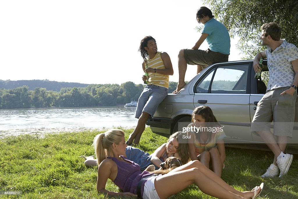 group of friends hanging out outdoors by a car : Stock Photo