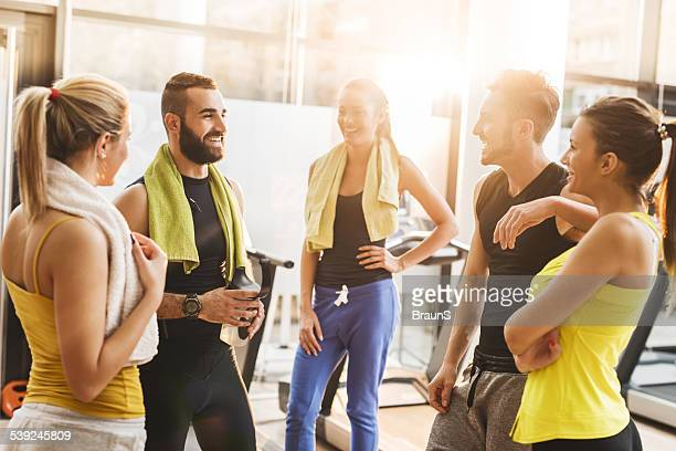 Group of friends having a break in gym and talking.
