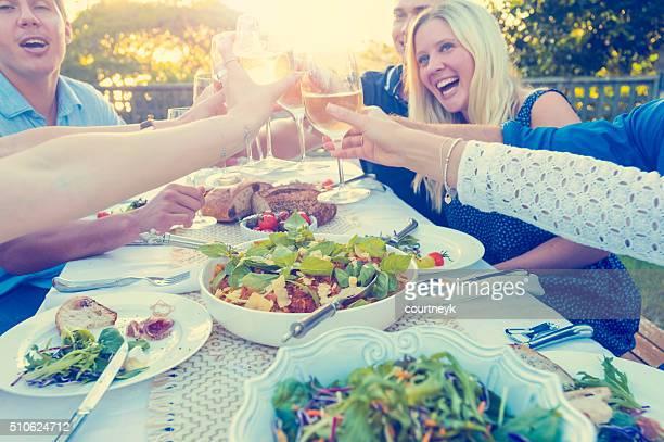 Gruppo di amici che avendo un pasto all'aperto.