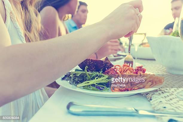 Gruppo di amici che avendo un pasto all'aperto