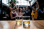 Group of friends having drinks at a bar and having fun - focus on foreground