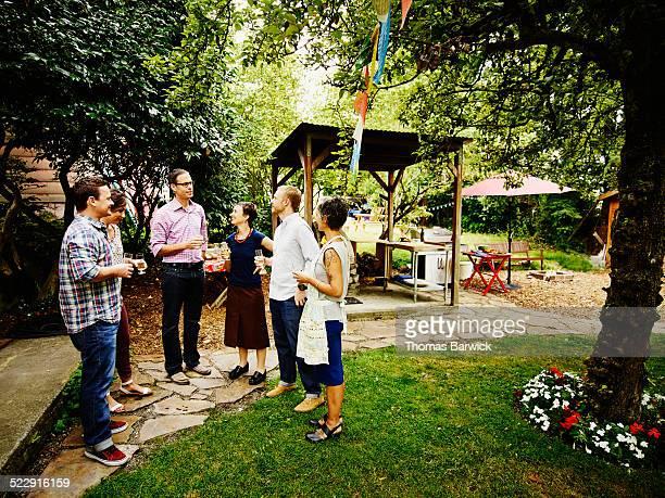 Group of friends having drinks in backyard