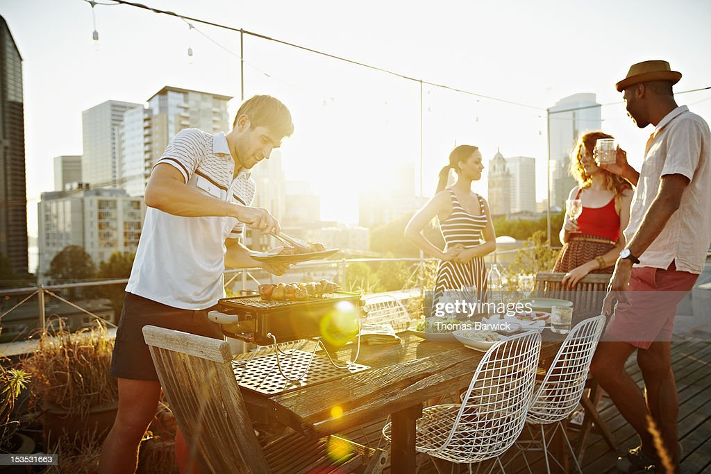 Group of friends having drinks on rooftop deck : Stock Photo