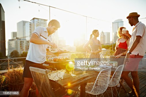 Group of friends having drinks on rooftop deck