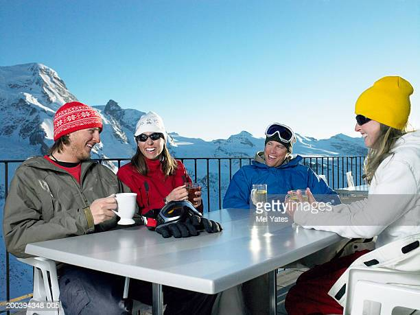 Group of friends having drinks outdoors, snowy mountains in background