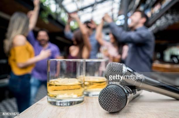Groupe d'amis s'amuser dans un bar karaoké