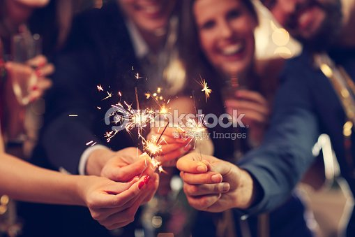 Group of friends having fun with sparklers : Stock Photo
