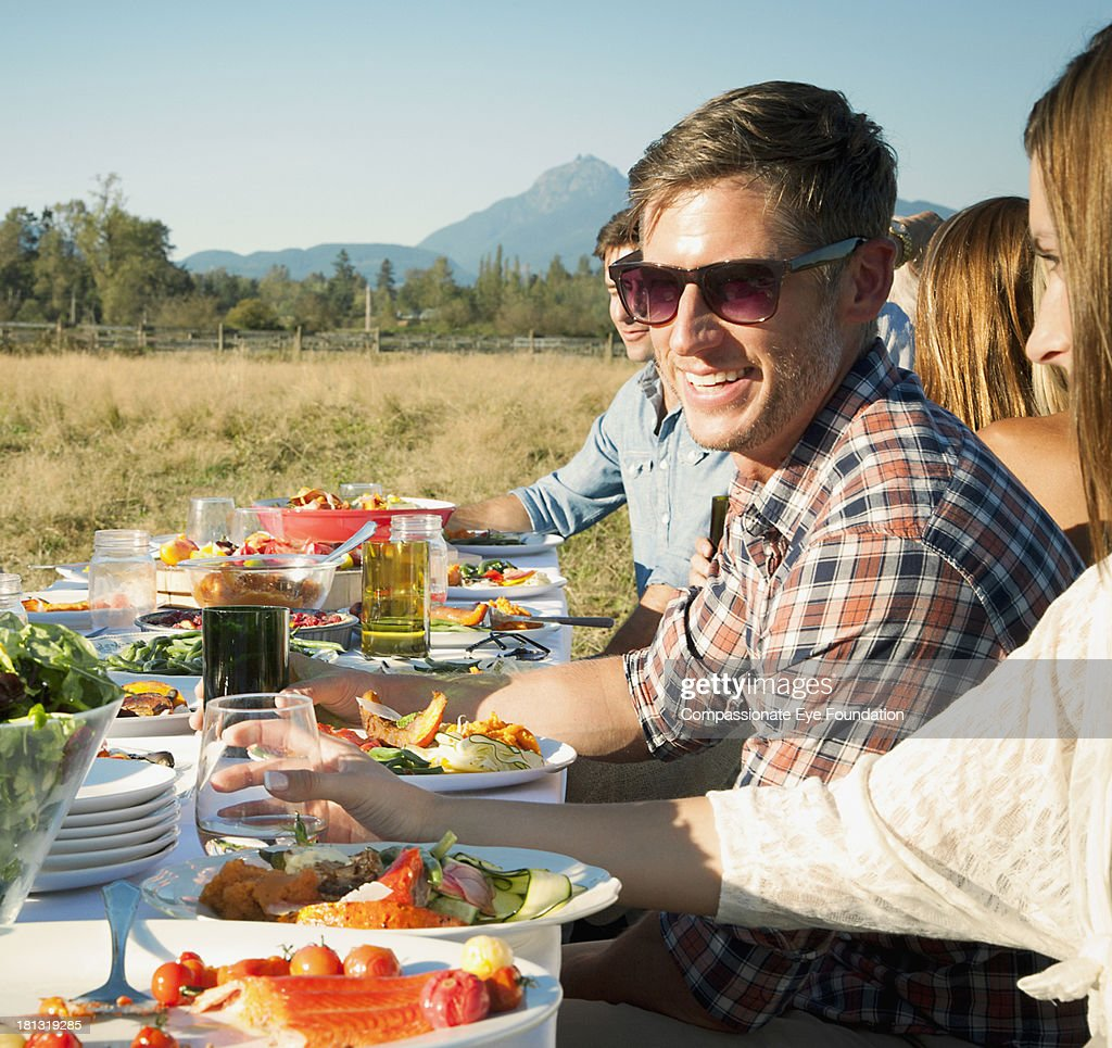 Group of friends having lunch outdoors stock photo getty for Group lunch