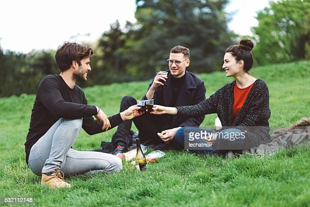 Gruppo di amici avendo pic-nic a Chaumont Parc des Buttes