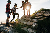 Group of friends hiking in mountain. Four hikers walking on a mountain at sunset.